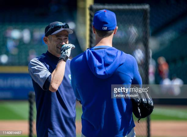 Former Seattle Mariners outfielder Ichiro Suzuki now an instructor with the team talks with Cole Hamels of the Chicago Cubs before the game against...