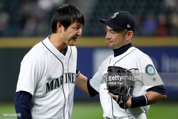 Former Seattle Mariners starting pitcher Hisahsi Iwakuma engages with Ichiro Suzuki of the Seattle Mariners after throwing out the ceremonial first...