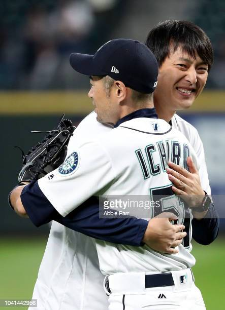 Former Seattle Mariners starting pitcher Hisahsi Iwakuma hugs Ichiro Suzuki of the Seattle Mariners after throwing out the ceremonial first pitch...
