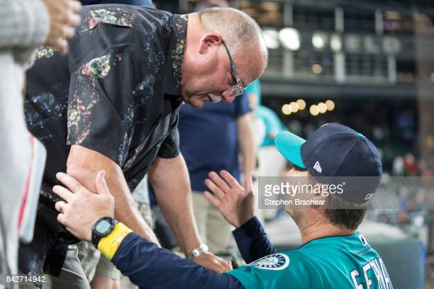 Former Seattle Seahawks head coach and former Green Bay Packers head coach Mike Holmgren and Seattle Mariners manager Scott Servais talk after a game...