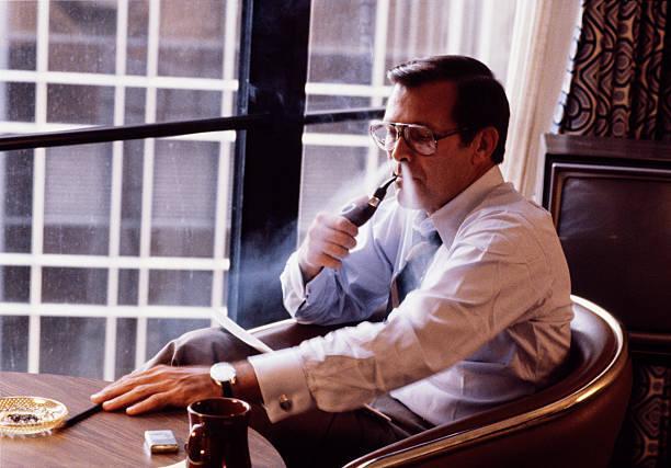 former-secretary-of-defense-donald-rumsfeld-smokes-his-pipe-in-his-picture-id594894397