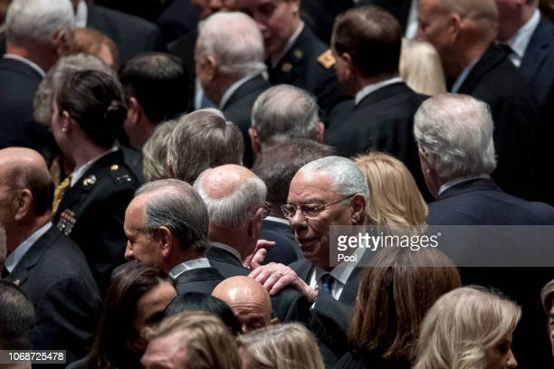 Former Secretary of State Colin Powell center right speaks to a guest before a State Funeral for former President George HW Bush at the National...
