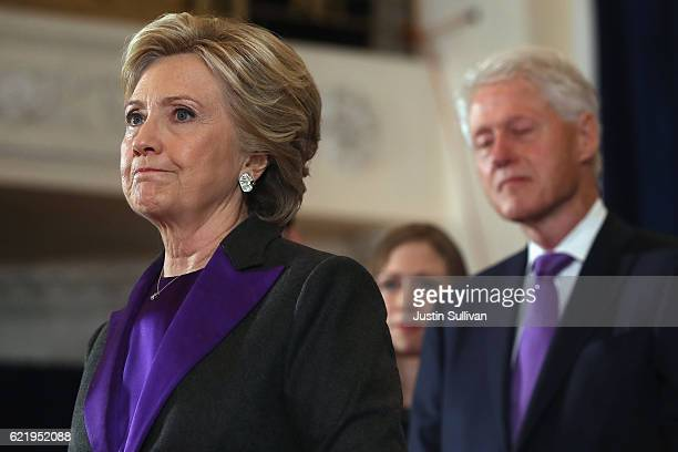 Former Secretary of State Hillary Clinton accompanied by her husband former President Bill Clinton pauses as she concedes the presidential election...