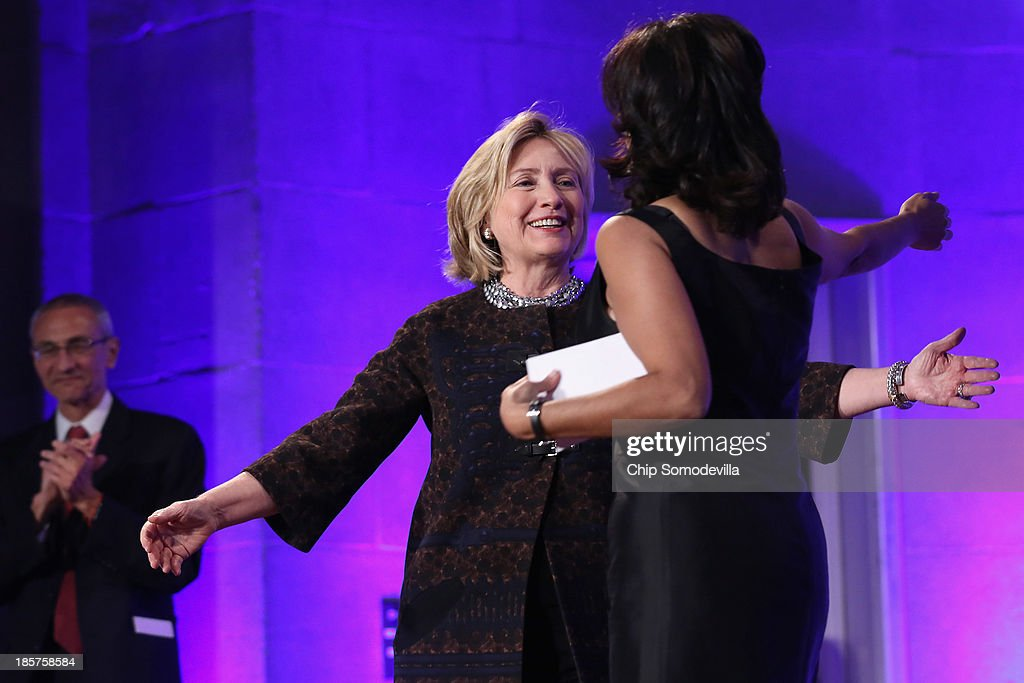 Former Secretary of State Hillary Clinton embraces Center for American Progress President Neera Tanden before adressing a gala celebrating the 10th anniversary of the center wit co-founder John Podesta (L) at the Mellon Auditorium October 24, 2013 in Washington, DC. Co-founded by former Clinton Administration Chief of Staff John Podesta, the liberal public policy research and advocacy organization is a think tank that rivals conservative policy groups, such as the Heritage Foundation and the American Enterprise Institute.