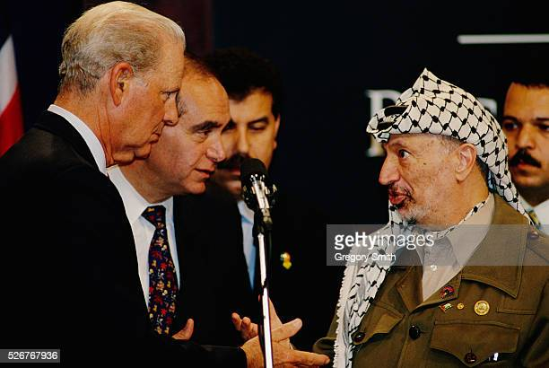 Former Secretary of State James Baker, Director of the Institute for Public Policy Edward Djerejian, and Palestinian leader Yasser Arafat converse at...