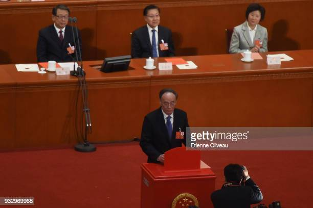 Former secretary of the Central Commission for Discipline Inspection Wang Qishan votes during the 5th plenary session of the first session of the...