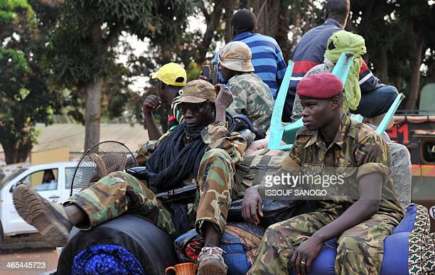 Former Seleka militants are escorted by French troops of the Sangaris Operation and MISCA peacekeepers out of the Camp de Roux in Bangui on their way...