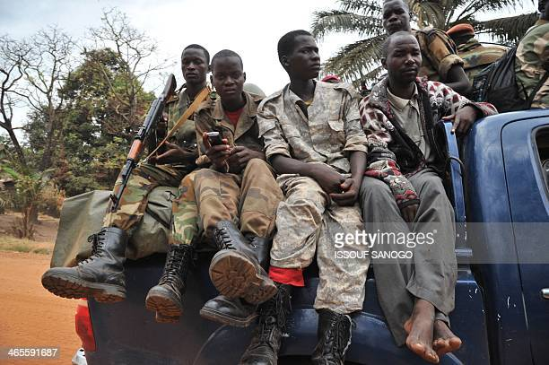 Former Seleka militants sit in a truck as they are escorted out of Kasai military camp in Bangui on their way to another camp outside the city on...