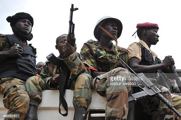 Former Seleka militants sit in the back of a truck as they are escorted out of Kasai military camp in Bangui on their way to another camp outside the...