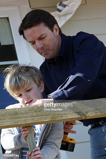 Former Sen John Edwards and his son Jack work on a Habitat for Humanity house after a press conference announcing that is he withdrawing from the...