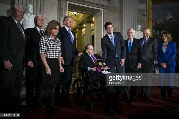 Former Senate Majority Leader Bob Dole center holds a Congressional Gold Medal while sitting for a photograph with House Minority Whip Steny Hoyer a...