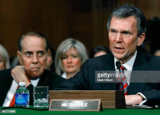 Former Senate Majority Leader Tom Daschle is flanked former Senate Majority Leader Bob Dole and his wife Linda Daschle as he testifies during his...
