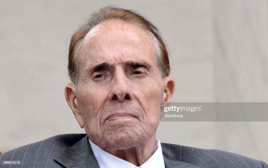 Former Senator Bob Dole listens as U.S. President Donald Trump, not pictured, speaks at a wreath laying ceremony at the Tomb of the Unknown Soldier at Arlington National Cemetery in Arlington, Virginia, U.S., on Monday, May 29, 2017. On Memorial Day, Trump visited Arlington National Cemetery to honor the memory of fallen service men and women. Photographer: Olivier Douliery/Pool via Bloomberg