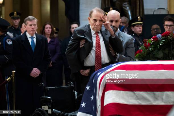 Former Senator Bob Dole stands up and salutes the casket of the late former President George HW Bush as he lies in state at the US Capitol December 4...