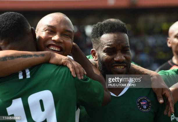Former Senegalese striker El Hadji Diouf hugs a colleague and former Nigerian midfielder Austin Jay Jay Okocha during a testimonial match between...