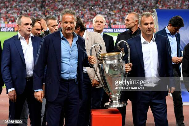 Former Serbian football stars Sinisa Mihajlovic and Dejan Savicevic pose with a replica of the Champions League trophy that Red Star Belgrade won in...