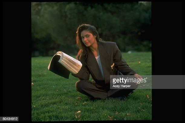 Former singer Vanity sitting on grass holding open Bible