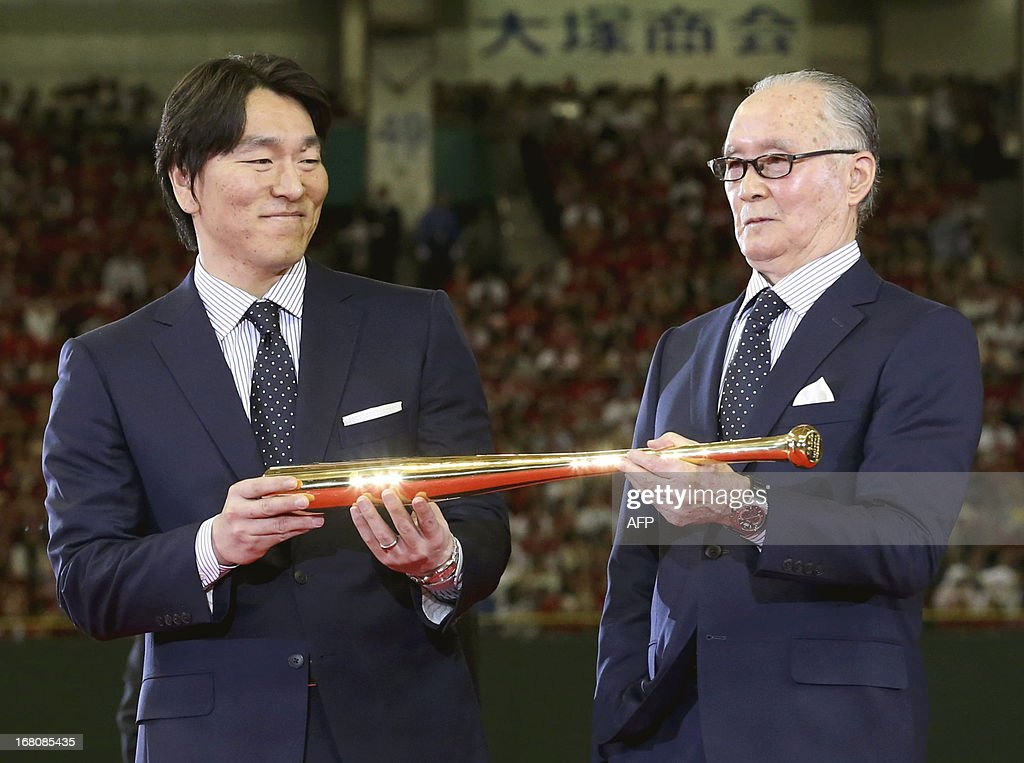 Former slugger with Japanese baseball's Yomiuri Giants, Shigeo Nagashima (R), accompanied by former Yomiuri Giants and New York Yankees outfielder Hideki Matsui (L), holds a golden bat presented by Prime Minister Shinzo Abe (not pictured) during a ceremony at the Tokyo Dome in Tokyo on May 5, 2013. Matsui and Nagashima received the 'People's Honour Award' from Prime Minister Shinzo Abe at the Tokyo Dome stadium. Nagashima, 77, venerated in Japan as a national hero, played and managed the Yomiuri Giants. JAPAN OUT AFP PHOTO / POOL / Tsuyoshi Matsumoto