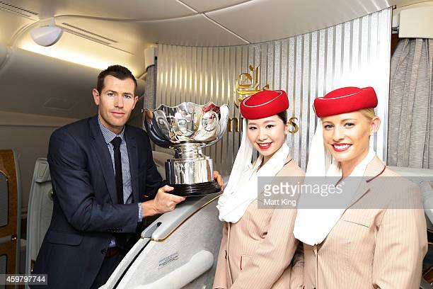 Former Socceroos Brett Emerton and Emirates cabin crew pose with the Asian Cup trophy after its arrival on an Emirates A380 during the Asian Cup...