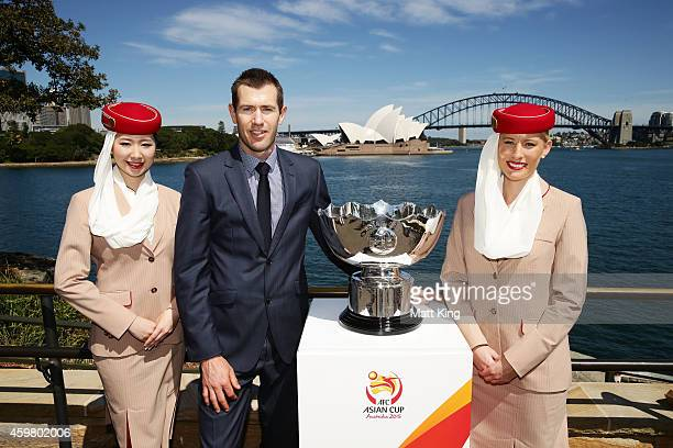 Former Socceroos Brett Emerton and Emirates cabin crew pose with the Asian Cup trophy during the Asian Cup Trophy Tour at Sydney Harbour on December...