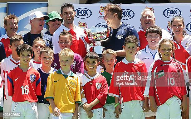 Former Socceroos players and Fox Sports presenters pose with the Asian Cup trophy during the Fox Sports Asian Cup coverage launch at Bondi Beach on...