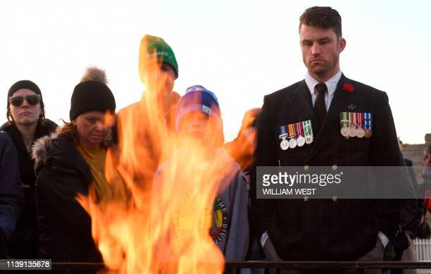 Former soldier looks into the Enternal Flame at the Shrine of Remembrance after the Anzac Day dawn service in Melbourne on April 25, 2019. - Dawn...