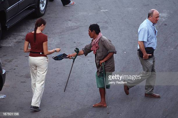 A former soldier who lost his leg to a landmine begs for money from foreign passersby near the riverfront in Phnom Penh