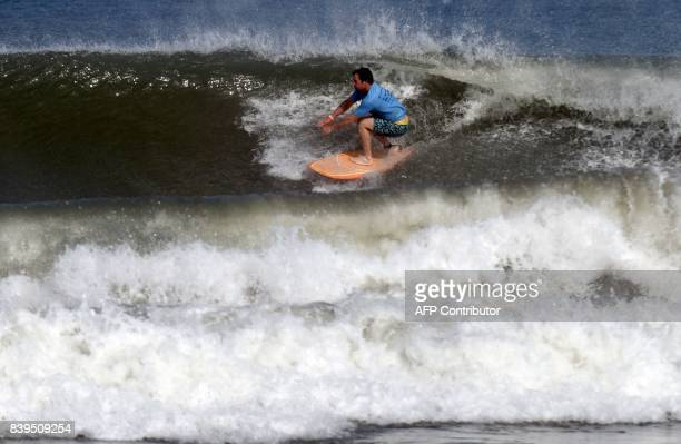 Former South African cricketer Jonty Rhodes surfs during the annual Covelong Point Classic Surf festival at Kovalam on the outskirts of Chennai on...