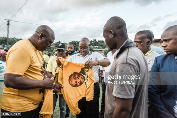 Former South African President and former president of the ruling party African National Congress Jacob Zuma handhovers an ANC tshirt to local...