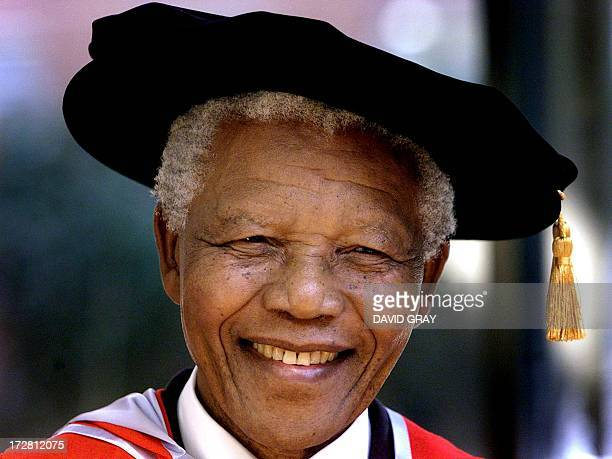 Former South African president and Nobel Peace Prize laureate Nelson Mandela wears a traditional mortar board while receiving two honourary...