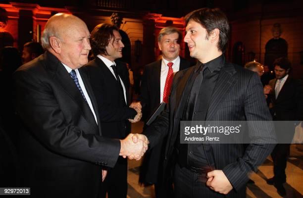 Former South African President Frederik Willem de Klerk shakes hands with Michele Malenotti vice president of Belstaff at the gala dinner BELSTAFF...