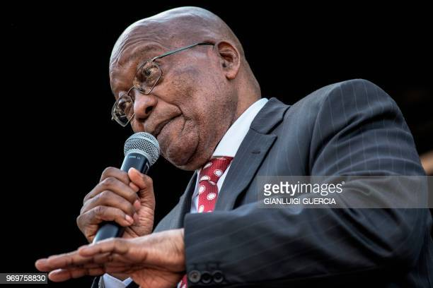 Former South African President Jacob Zuma gestures as he delivers a speech during a rally in his support outside the High Court, in Durban on June 8,...