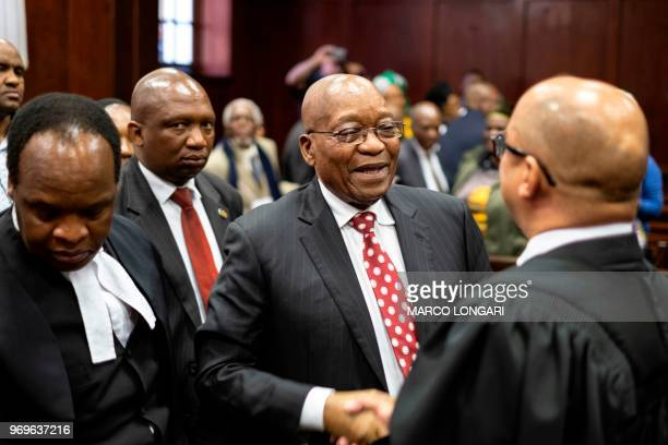 Former South African President Jacob Zuma greets his team at the end of the hearing at the Durban Magistrate Court in Durban, on June 8, 2018. - He...