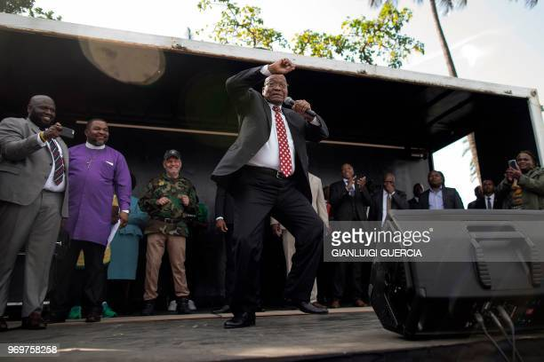 Former South African President Jacob Zuma sings and dances on stage after delivering a speech during a rally in his support outside the High Court,...