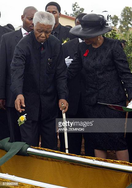 Former South African president Nelson Mandela accompanied by his wife Graca machel throws a rose on the grave of his son Makgatho in his village Qunu...