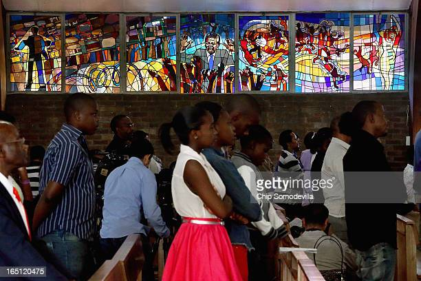 Former South African President Nelson Mandela and the struggle against apartheid are depicted in a stained glass window as congregants pray during...