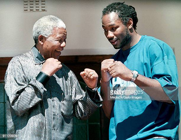 Former South African president Nelson Mandela and world heavyweight boxer Lennox Lewis take up boxing stances in a mock fight at Mandela's residence...