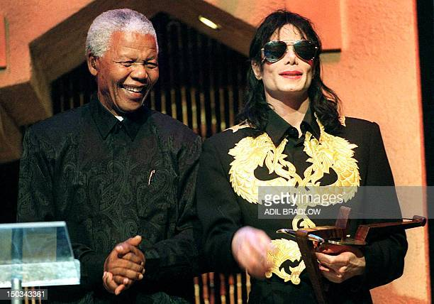 Former South African President Nelson Mandela claps his hands after American popicon Michael Jackson was given a lifetime achievement award during...