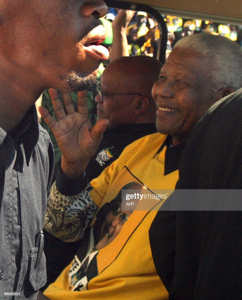 Former South African President Nelson Mandela, flanked by ANC leader and presidential favourite Jacob Zuma (C/background) greets supporters in Johannesburg at Ellis Park stadium on April 19, 2009 at the final African National Congress election rally. Nelson Mandela Sunday reminded the ANC of its duty to eradicate poverty and urged unity in a surprise appearance