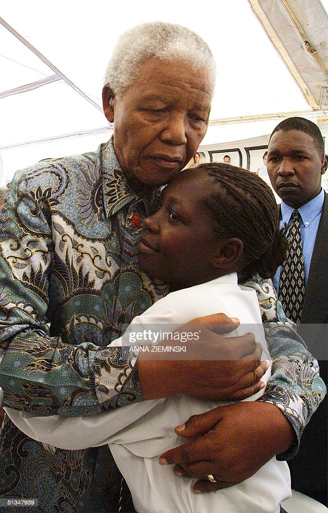 Former South African president Nelson Mandela hugs Babalwa Tembani (20), who was infected with the HIV virus after being raped by her uncle at the age of 14, at the Nolungile Clinic at Site C in Khayelitsha, Cape Town 12 December 2002. She is currently on ante-retroviral treatment and is involved in education work in schools and youth centres. Nelson Mandela visited the clinic which is run by Medecins Sans Frontiers and is the first site in South Africa where ante-retroviral treatment is offered for free in public community centres.