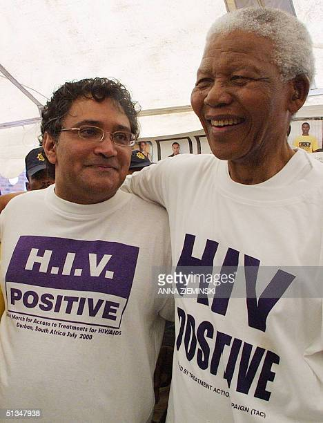 Former South African president Nelson Mandela puts his arm around Zackie Achmat an HIV Positive member of the Treatment Action Campaign after...