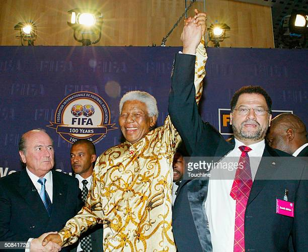 Former South African President Nelson Mandela's hand is held high by Bid CEO Danny Jordaan and FIFA President Sepp Blatter during the FIFA 2010 World...