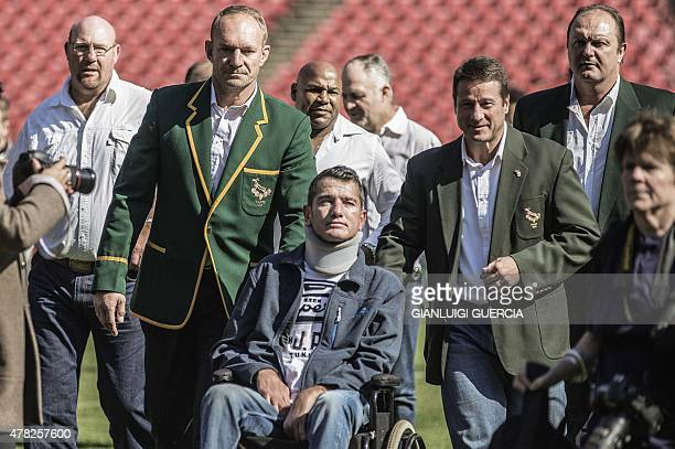 Former South African Rugby World Cup winner team Captain Francois Pienaar assists former teammate flyhalf Joost van der Westhuizen during a...