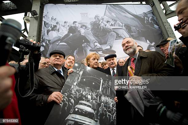 Former Soviet leader Mikhail Gorbachev German Chancellor Angela Merkel and Former Polish president Lech Walesa hold a signed print of people crossing...