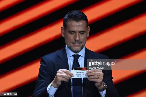 Former Spanish footballer Andres Palop shows the paper slip of England's West Ham United FC during the draw for the UEFA Europa League football...