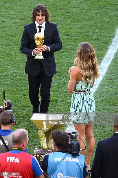 Former Spanish international Carles Puyol and model Gisele Bundchen present the World Cup trophy prior to the 2014 FIFA World Cup Brazil Final match...