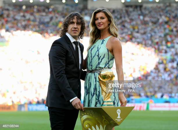Former Spanish international Carles Puyol and model Gisele Bundchen present the World Cup from a Louis Vuitton travel case prior to the 2014 FIFA...