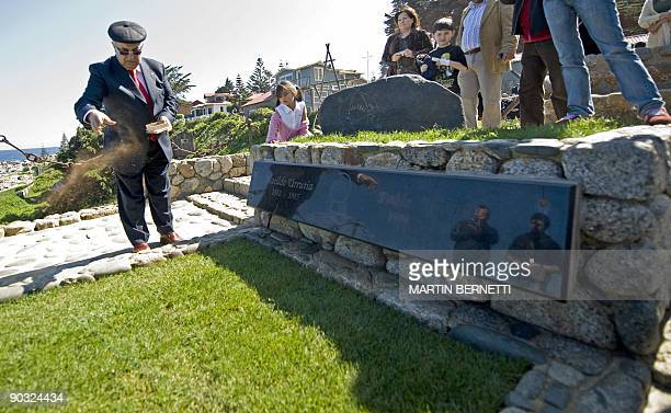Former Spanish refugee Jose Gallego Rua scatters a handful of soil from his native land over the grave of late Chilean poet Pablo Neruda at his...