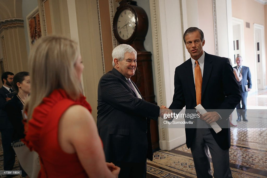Former Speaker of the House Newt Gingrich (R-GA) (C) shakes hands with Sen. John Thune (R-SC) just off the floor of the Senate in the U.S. Capitol May 18, 2015 in Washington, DC. Senate Majority Leader Mitch McConnell (R-KY) said that he will postpone the Senate's Memorial Day recess until lawmakers tackle a trade bill, renewal of the Patriot Act and funding for federal highways.