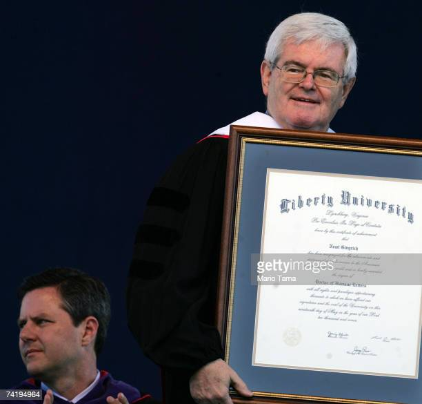 Former Speaker of the House of Representatives Newt Gingrich holds his honorary degree as Jerry Falwell Jr looks on during the school's 34th...